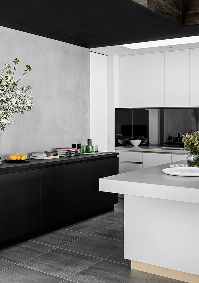 Fingerprint-proof black and white laminated joinery, with concrete style benchtops and brass accents.