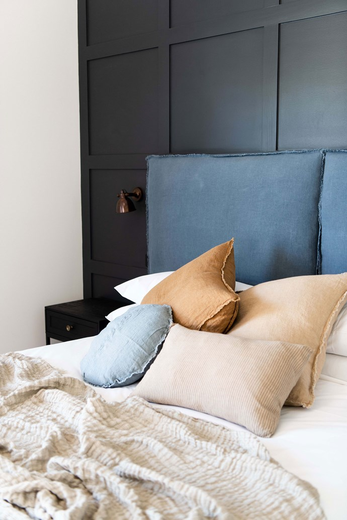 A comfy stack of linen throw cushions adorn the bed.