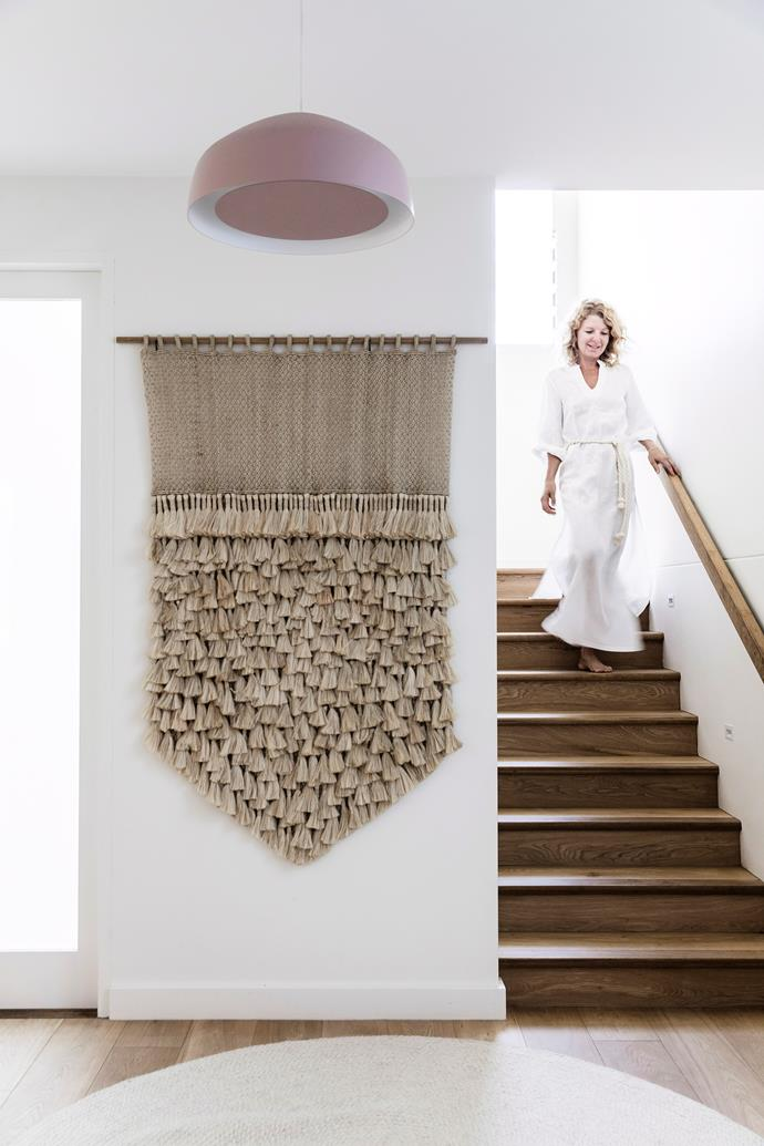 An enormous woven wall hanging makes a statement at the bottom of the stairs.