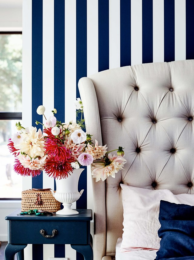"A vase of brightly coloured dahlias, Billy buttons (woolly heads) and ranunculus, pops against the navy blue striped wallpaper in the bedroom of this [recycled brick farmhouse](https://www.homestolove.com.au/recycled-brick-house-20262|target=""_blank"")."