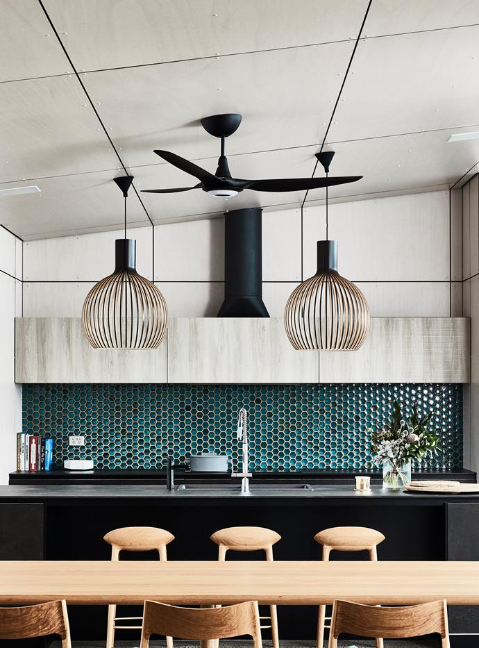 A swathe of glossy honeycomb tiles is a key ingredient in the recipe for a darkly delicious kitchen area designed by Richard Cole Architecture and Snaidero.