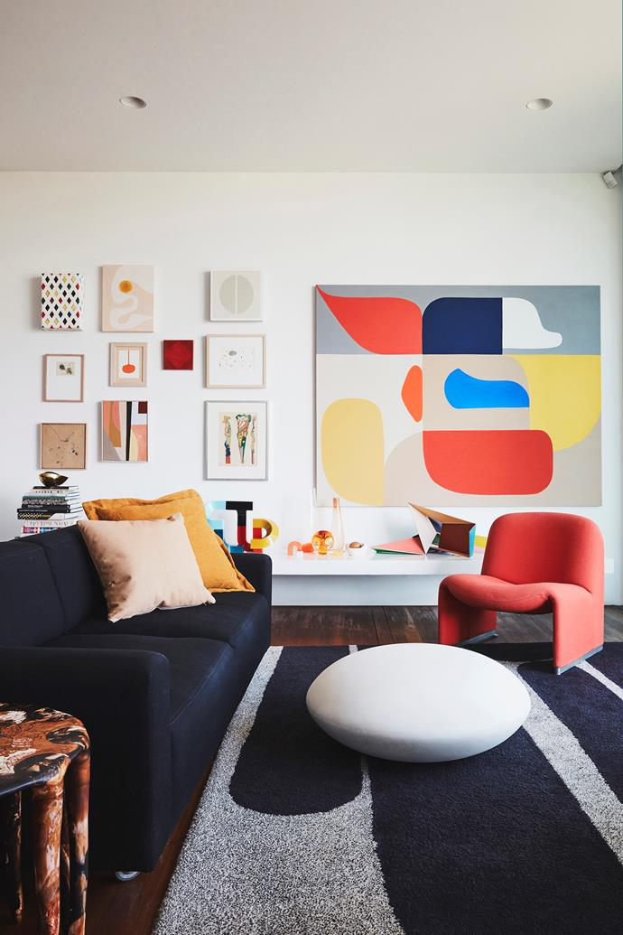 In the living area of this home belonging to Dinosaur Designs co-founders Louise Olsen and Stephen Ormandy, a red Paul Poulain chair and Michael Young for Cappellini floor seat sit atop a Dinosaur Designs x Designer Rugs 'Sticks' rug. A large artwork by Stephen commands attention from the wall.