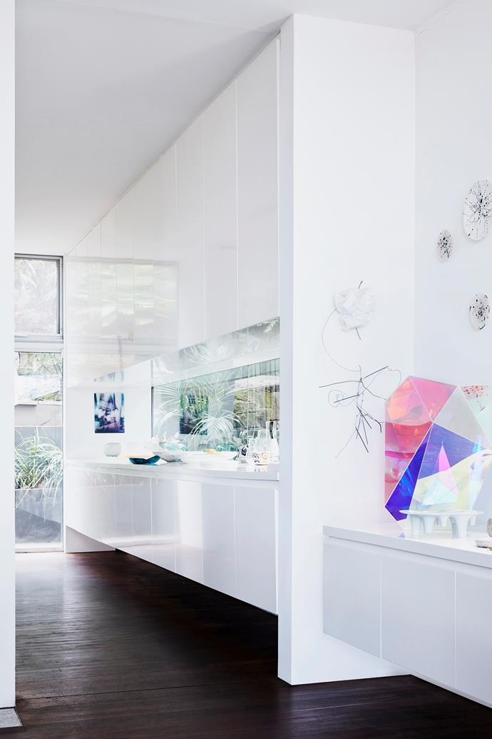 The contemporary kitchen is fitted with white melamine cabinetry and a stainless steel mirrored splashback. The Boulder sculpture by Gemma Smith brings a splash of colour to the space.