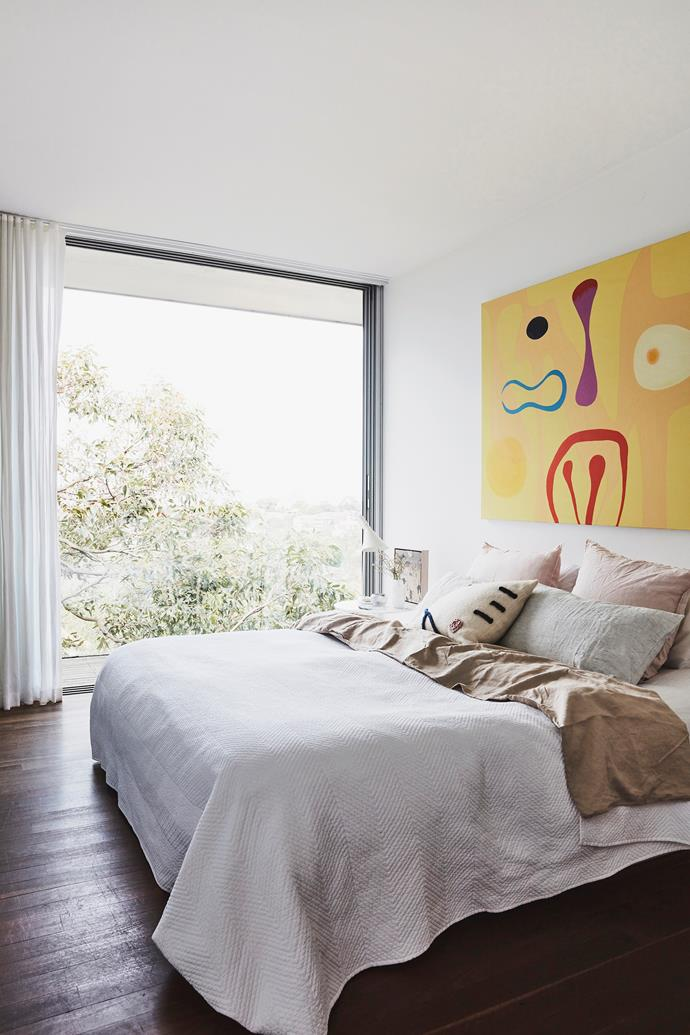 "Our home sits up among the trees,"" says Louise, with the bush view evident from their bedroom window. ""There's something therapeutic about being close to nature."" The bed is made with Cultiver sheets, while a bold artwork by Stephen brings a pop of colour."