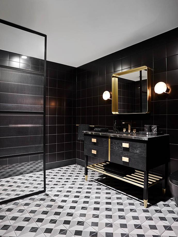 "Designer Greg Natale says, ""This client loves dark spaces. This ensuite bathroom is in the children's wing of the house so we took the brief of creating a moody, dramatic interior and layered it with a fun, oversized geometric pattern on repeat."" He says it is always worth investing in the best tiles you can afford, and has used tiles from his own collection in this space."