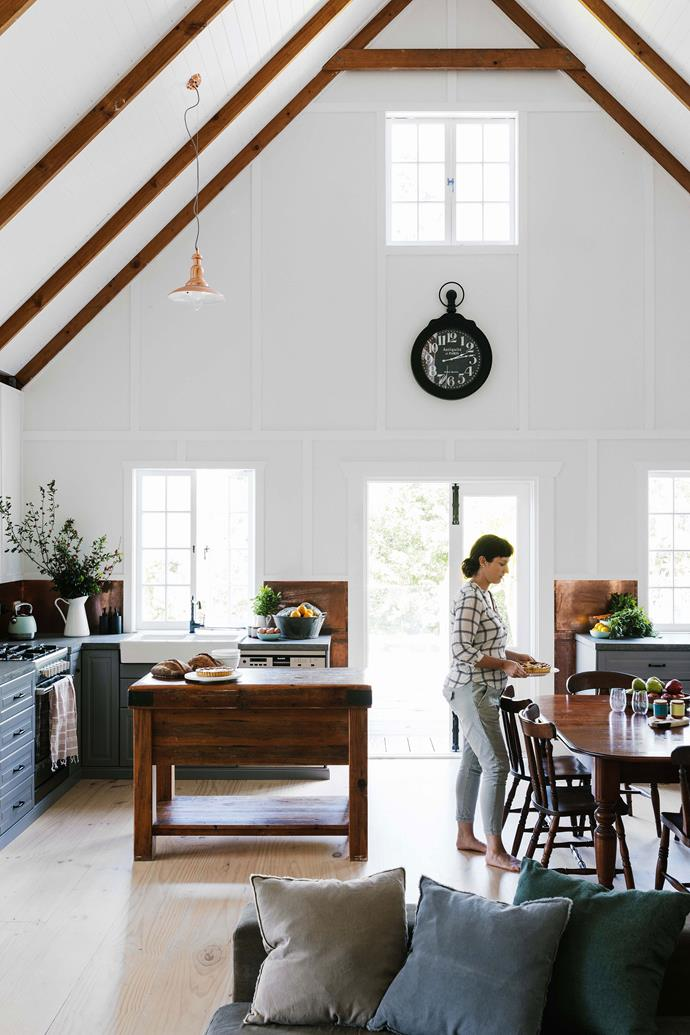 A copper splash back, hand-poured concrete bench tops, and a vintage timber island make this kitchen feel like a custom build.