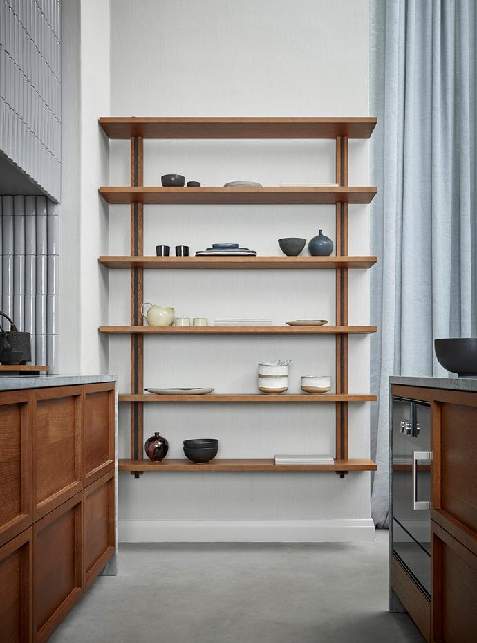 The repetition of clean shelf lines and slim, rounded wall tiles makes the space feel taller. Bonus: this open shelving is multifunctional because it can be reconfigured.