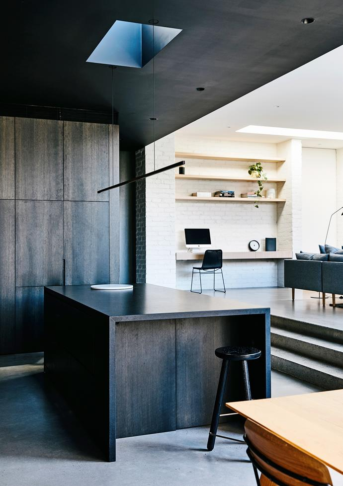 "A ""Highline"" LED pendant light designed by Archier hangs above the oversized black granite island bench."