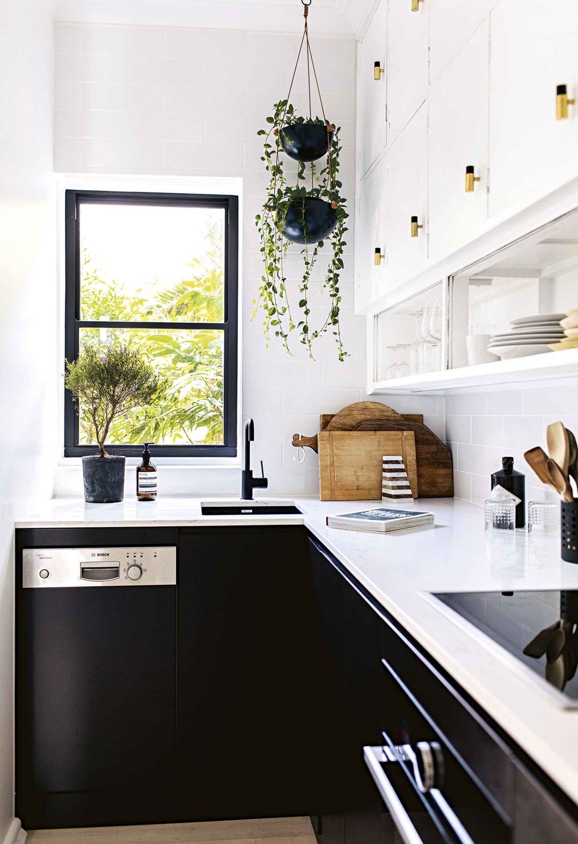 Updating your cabinetry hardware can make a huge difference for little cost. Here, the wall cabinets were updated with Anthropologie handles. A window frame painted in black allows the view to pop.