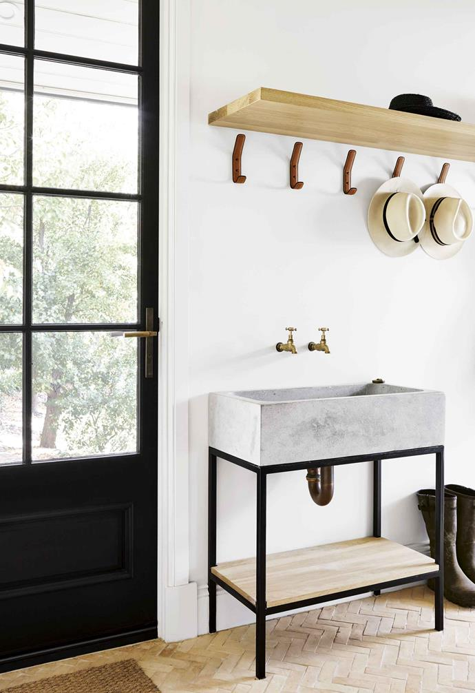 A concrete sink with timber and steel frame brings a clean, utilitarian feel to a mudroom. Simple brass tapware completes the look without drawing attention away from the sink. For minimal splashing, choose a wide deep design.