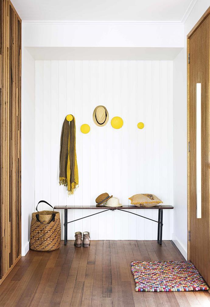 "A narrow bench seat in the entrance of this [timber-clad sustainable home](https://www.homestolove.com.au/timber-clad-sustainable-house-17545|target=""_blank"") is paired with bright yellow Muuto wall hooks to create a simple mudroom area."
