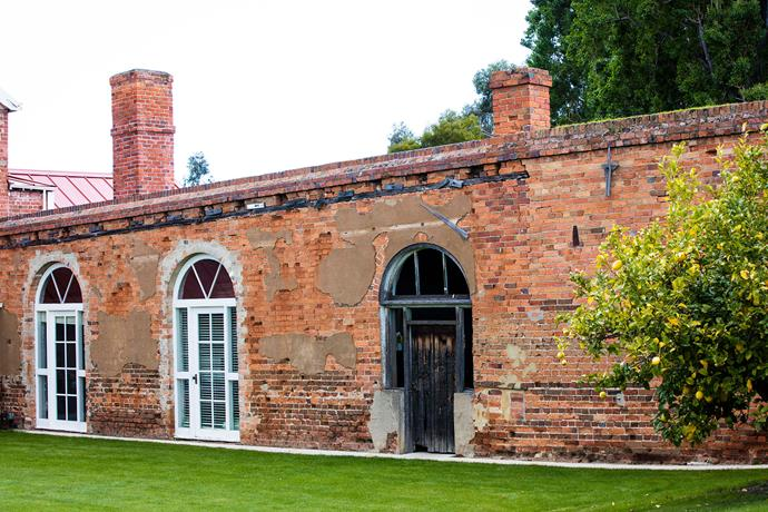 Arched doorways in the brick wall open to the house as well as to other sections of the garden.