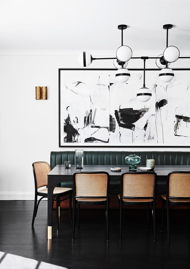 "The owner of this [Art Deco home](https://www.homestolove.com.au/modern-art-deco-home-20290|target=""_blank"") enlisted furniture maker Tim Noone to create her Curatorial dining table, with the custom banquette and Thonet 'Hoffmann' chairs providing seating for 10. A limited-edition Peggy chandelier by Hangar Design Group hangs above. The triptych artwork is by Antonia Mrljak."