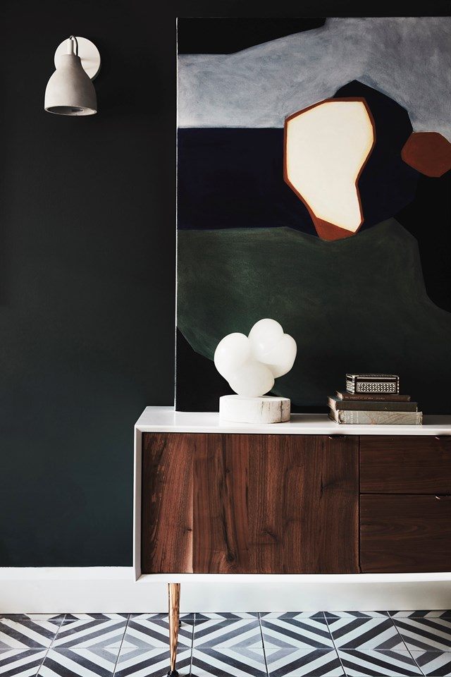 "If you're not allowed or simply prefer not to hang art on the wall, a sideboard provides the perfect place to display your works. Here, a large painting by Katie Cridge atop a retro-style console makes a statement in the entryway of this [Art Deco home](https://www.homestolove.com.au/modern-art-deco-home-20290|target=""_blank"")."