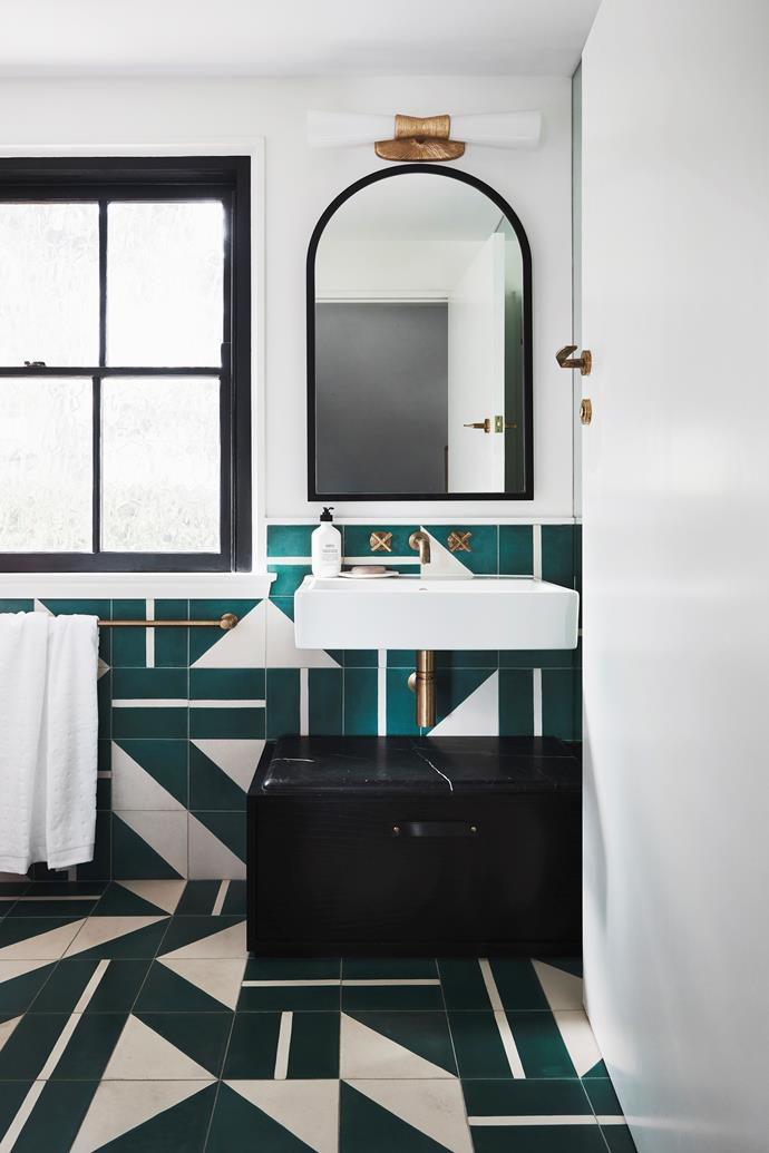 "Two different types of Brasilia tiles from Popham Design were used to create this eye-catching pattern in the powder room. Storage is hidden behind a mirror, which is beneath a Kelly Wearstler 'Utopia' sconce, while towels are kept in the trunk. Sophie says the brass accents feel ""solid and handsome""."