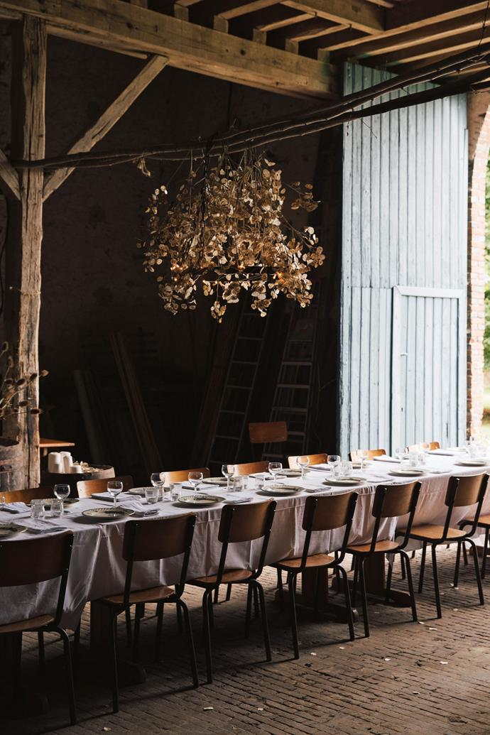 "The [barn transformed](https://www.homestolove.com.au/home-conversion-ideas-19765|target=""_blank"") for a long lunch with desks from the local school. ""My dad couldn't believe the photographs of his barn, where he parks his old tractor, transformed into a grand dining room with flowers and a long table for 23 people,"" says Flore, with a smile."