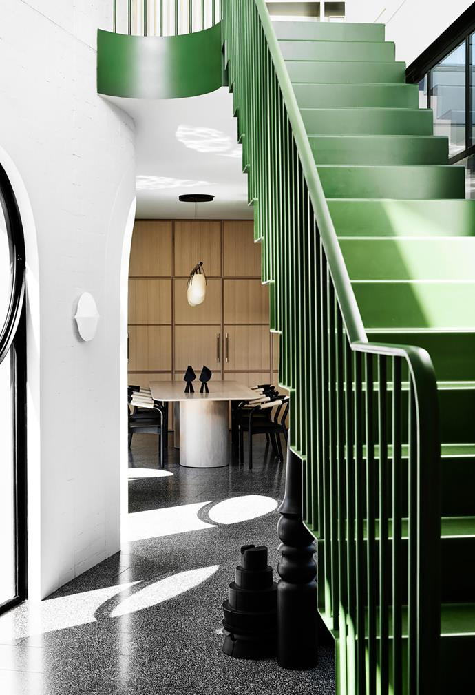 The green-hued stairs lead to the second storey where there is a large study, parents' zone and deck. Timber floor sculptures by Jo Wilson sit in the passageway to the kitchen and dining area in the new pavilion. Shimmering reflections from the swimming pool can be seen on the ceiling.