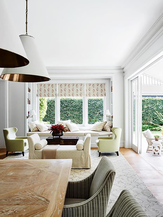 In the family room, custom-made table with chairs upholstered in Perennials 'Soho Stripe' from South Pacific Fabrics. Rug from Behruz Studio. Visual Comfort 'Goodman' pendants from Laura Kincade.