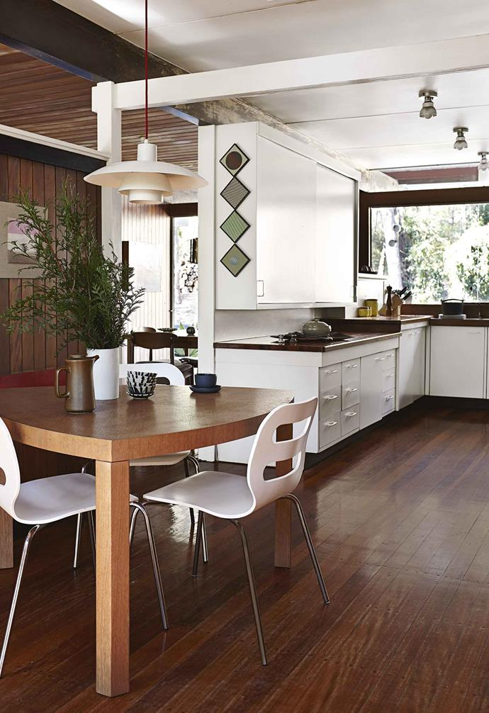 "They own Ryan Renshaw Gallery in Brisbane and love to experiment with artists' works in their own domestic setting. ""The house is a second showroom,"" says Ryan. ""We love entertaining here among the art.""<br><br>**Kitchen** One of the first items purchased by Ryan and Danielle for the house was an imported Louis Poulsen 'PH 4/3' light, available from Living Edge. Ryan and Danielle have kept the original kitchen, which is still in working order. Architect Robin Spencer had the foresight to create extra-wide benchtops with deep cabinets to suit his family and future generations to come. Artwork: *The Tyranny of Infinity* by Chris Bond."