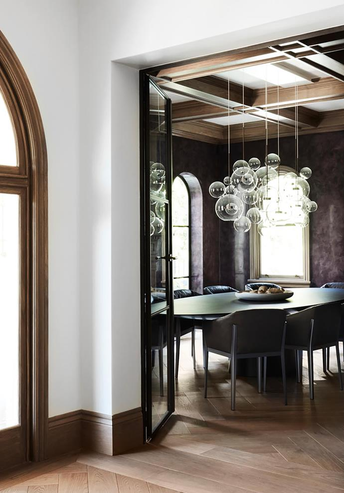 The walls of the formal dining room are finished in deep grape-coloured stucco lustre. The Emmemobili 12-seater dining table is ringed by Cassina leather chairs. Giopato & Coombes 'Bolle' light fitting.