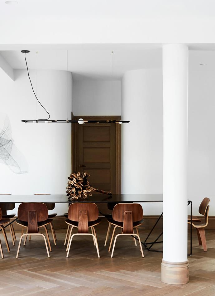 The casual dining area has a 'Fineline' custom extension table from Specified Store with Charles and Ray Eames dining chairs.  Light fitting by Lambert & Fils. Wall sculpture from LuMu Interiors.