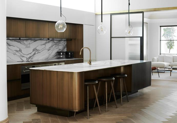The kitchen has burnished brass-finished cupboards and Calacatta Gold marble, leather and brass accents. Matter Made bar stools. Viabizzuno 'Sul Sole Va' lights.