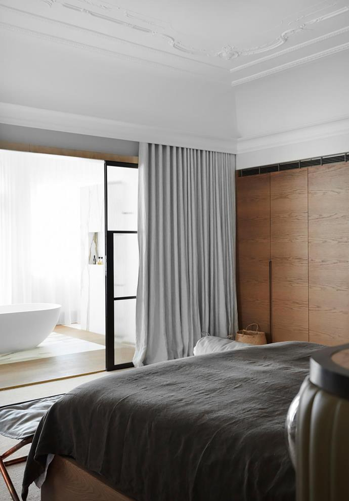 The main bedroom has a custom bedhead in fluted olive leather and smoked oak joinery. Linen drapes from Simple Studio. Society bed linen from Ondene. Baxter ottoman.