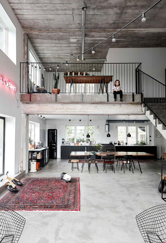 **Dining area and mezzanine** The concrete ceilings and floors feel industrial and reference the original factory flavour. Nita's son Helmer looks down from the upstairs landing.