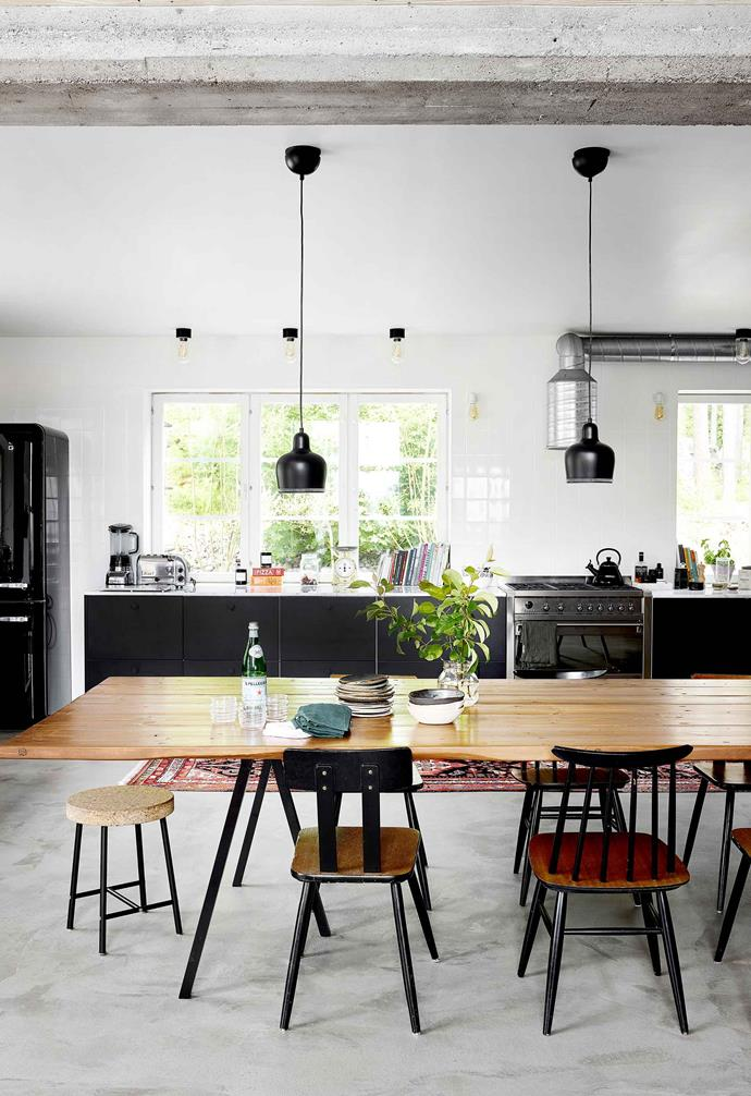 **Kitchen and dining area** The table was built by a carpenter friend using 3.5m floorboards and Hay legs. The chairs are vintage and flea-market finds, while Artek pendants are suspended above.