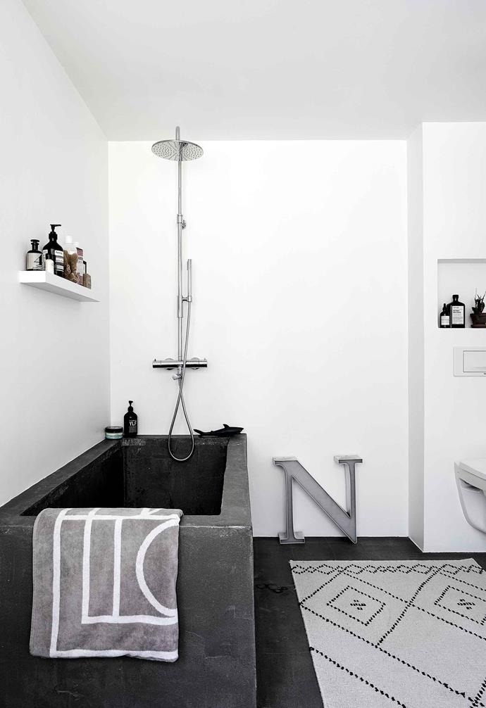 "**Bathroom** ""The walls are painted white because I couldn't decide whether to tile them,"" Nita admits. The large showerhead is from Tapwell and the rug was designed by Saana and Olli for Finnish brand Mum's."