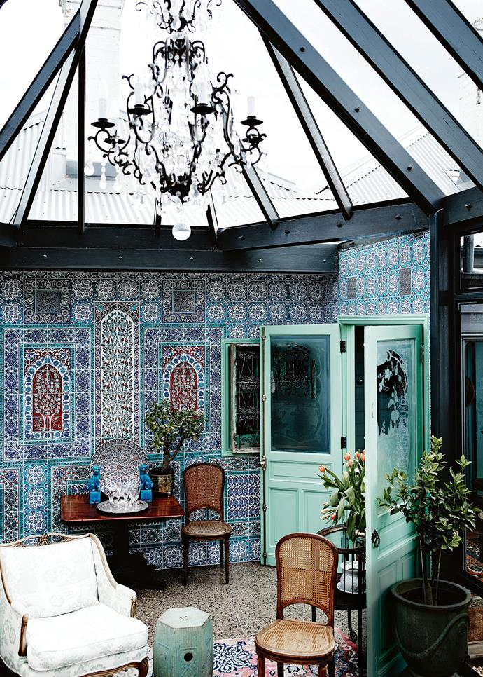 """The conservatory with its Turkish tiled walls, Regency side table and 1920s rattan chairs. """"The building of the conservatory was a response to the beautiful garden,"""" Jeff says, adding that the work scheduled to take four months blew out to two years. """"It has 26 opening windows… A bottomless pit of money went into this room but I'm thrilled with it — it's the gin and tonic room!"""""""