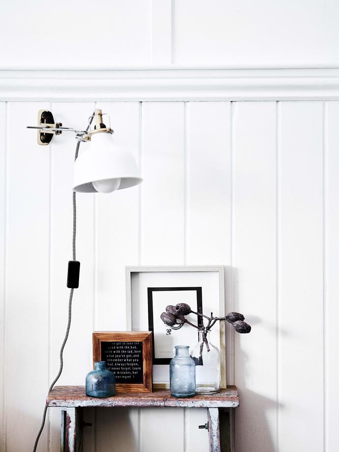 "A second-hand mix of objects found at garage sales and gifts from friends sit atop a ladder Amanda Britt inherited from her great-grandfather. The Ranarp wall lamp is from [IKEA](https://fave.co/2WxH8xu|target=""_blank""