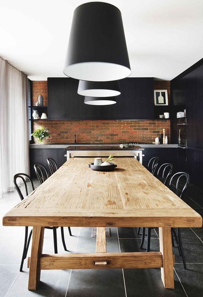 "A large blond timber table in the centre of the room, white ceilings and ample lighting keep [this kitchen](https://www.homestolove.com.au/cool-kitchen-smart-style-17179|target=""_blank"") feeling light and spacious despite a healthy dose of black."