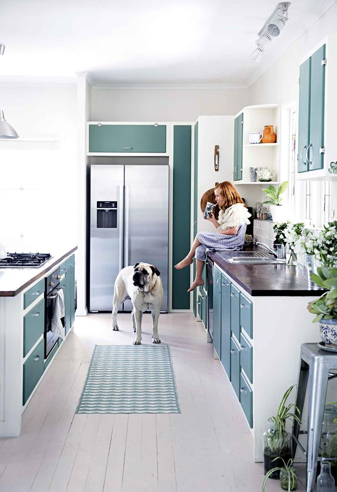 "The homeowner had the colour of a teatowel matched to create the paint for the cupboard doors in her kitchen to give the space a distinct vintage vibe. The pale teal colour is paired with steel door pulls that match the stainless steel [appliances](https://www.homestolove.com.au/colourful-kitchen-appliances-19988|target=""_blank"") for an industrial look in the heart of this [renovated worker's cottage](https://www.homestolove.com.au/10-creative-ideas-for-every-space-in-your-home-18004