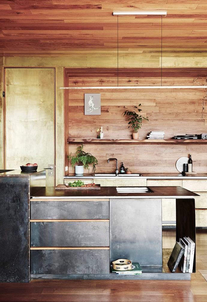 An eco home in Victoria features a timber clad ceiling, walls and flooring. Making a bold statement in the kitchen, textured gold paint has been used on the cabinetry, creating a warm and weathered finish.