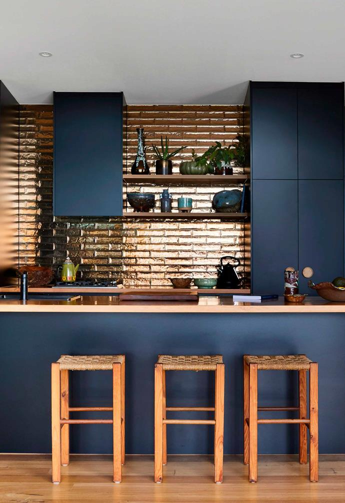 Dark navy cabinets create a stark contrast to the glossy and reflective copper subway tiles of the kitchens' splashback and the copper benchtops.