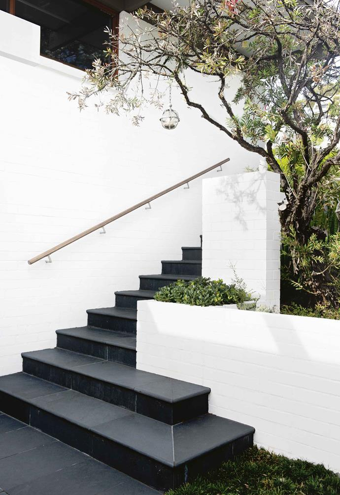 """""""It's not meant to be a low-maintenance garden,"""" says Michael. """"Alison and Ray enjoy working outdoors, but they also love to travel. It was designed so that they could leave the garden without needing a housesitter to do much, and then pick it up when they come back.""""<br><br>**Stairs** The stark white creates a dramatic contrast with the charcoal tiled stairs."""