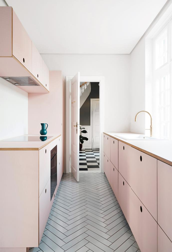 Pale grey subway tiles are laid in a herringbone pattern and is paired with stark white walls and ceiling. Blush pink cabinetry adds warmth to the space and is paired with an exposed timber edge.