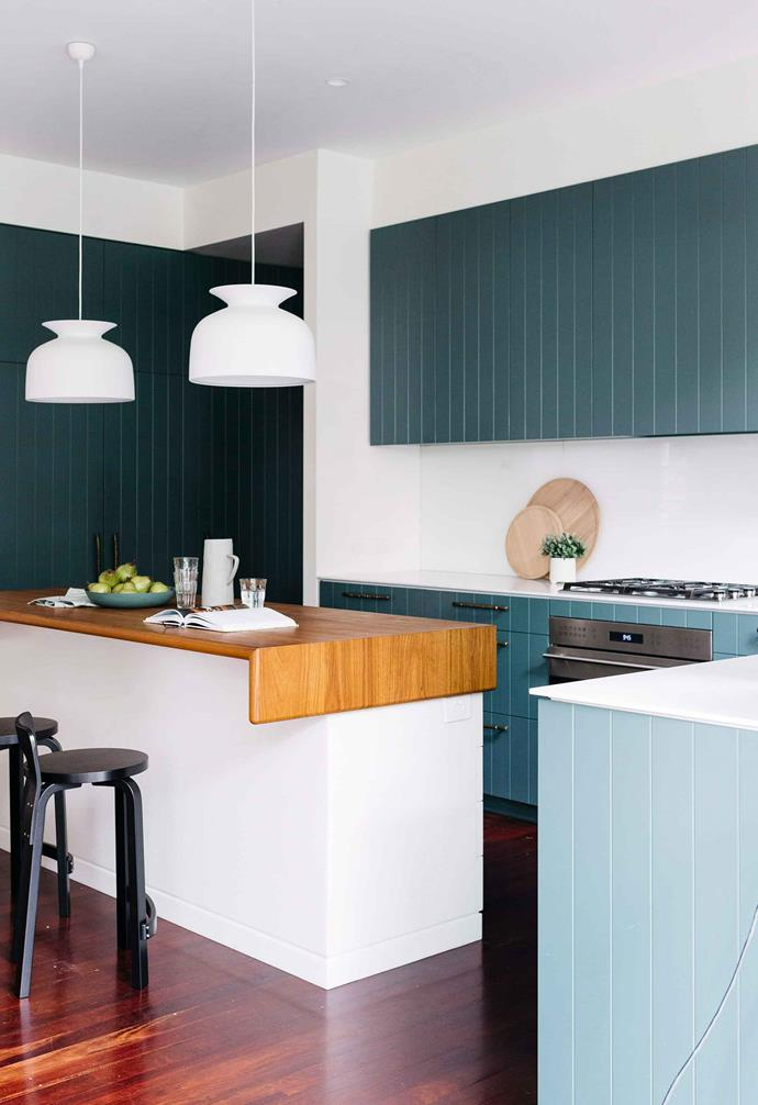 Timber panel cladding in this kitchen space is painted a vibrant teal colour and paired with black drawer pulls and stainless steel appliances.