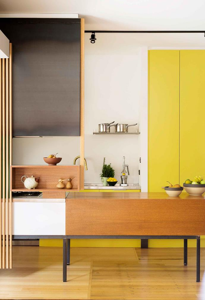 You don't have to go all out with bold kitchen cabinetry either - in this kitchen space the yellow cabinets are contrasted with timber shelving and additional white cabinets.