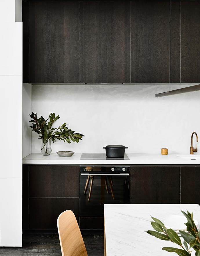 The benchtop and splashback are covered in an X-Bond polished bond by Alternative Surfaces, which isn't cold like regular concrete. Dark joinery in Porter's Paints Double Furnace. Icon tapware, Astra Walker. Fisher & Paykel appliances.