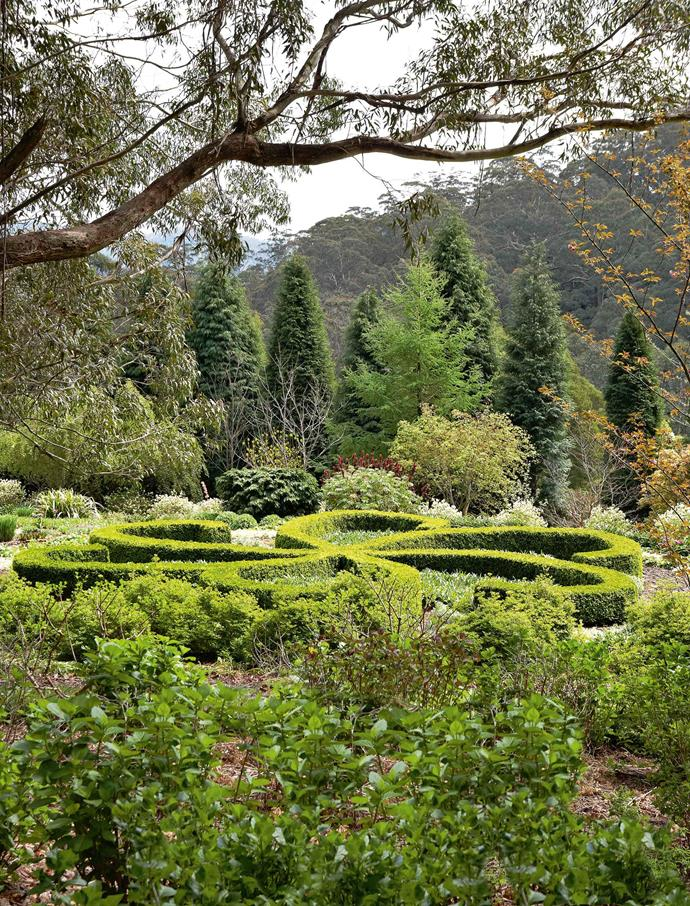 The flat section at the bottom of the hill contains some whimsical garden art in the form of a sensuously curving buxus parterre that looks like it might spin like a top. Against a background of conifers and shrubs, this striking parterre layout makes good use of the flat land at the bottom of the property.