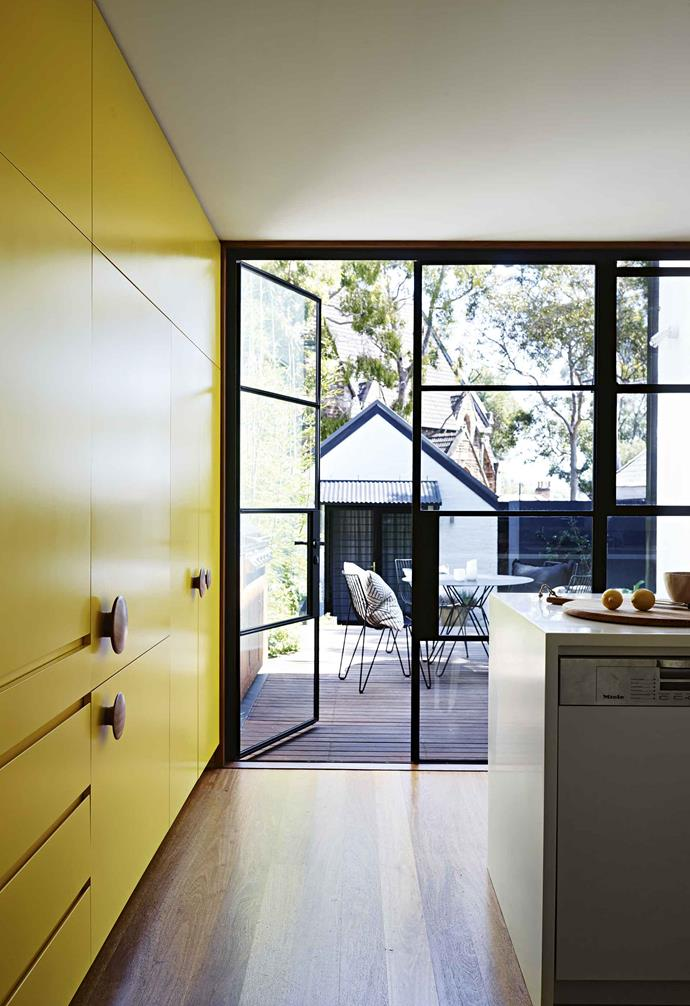 "There was a real lack of connection between the house and the backyard and deck area, as well as a desperate need to draw natural light into the rear of the home. ""We knew we wanted big windows to frame the view and to allow sunlight in,"" says Matthew.<br><br>**Storage** The joinery holds a breakfast nook, fridge and freezer, ""We narrowed it down to two shades,"" says Matthew of the yellow tone."