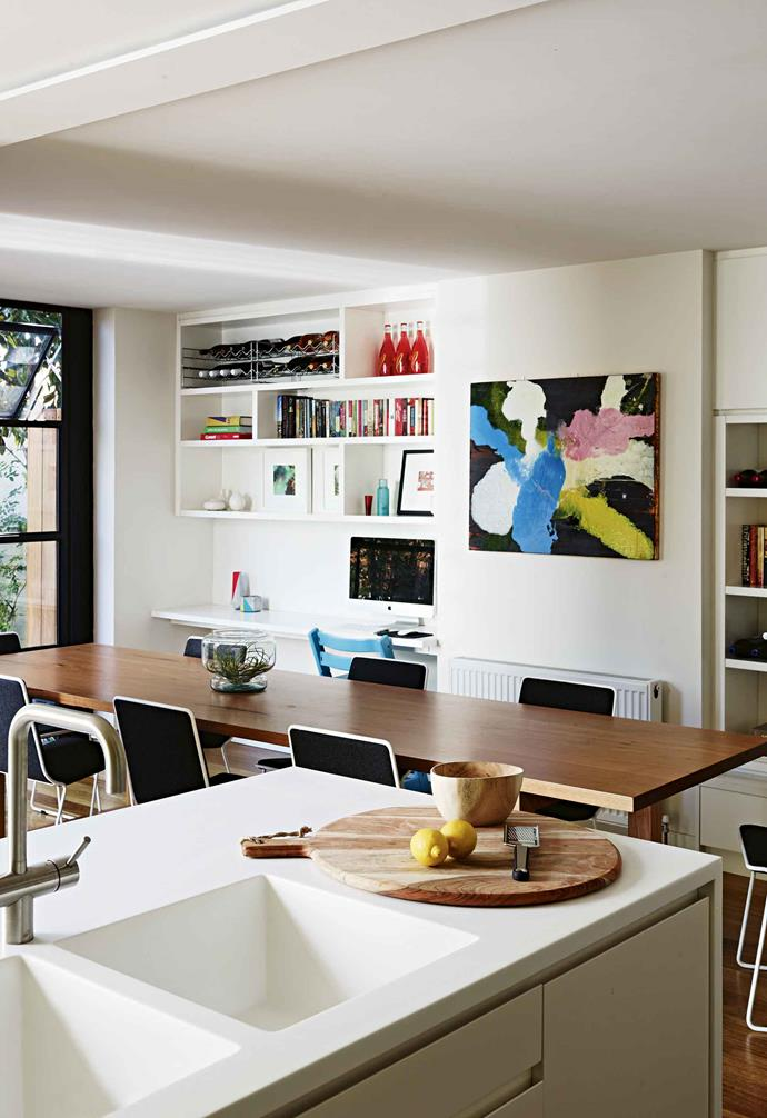 "One of her first solutions was to push the yellow joinery back against the party wall [a common boundary wall] to create storage for a breakfast nook, fridge and pantry. The door between the kitchen and corridor was taken out to allow the joinery to extend into the hallway, helping to enhance the space and sense of connectivity in the home.<br><br>**Kitchen/dining area** The wall separating the kitchen from the dining area was removed to create an open flow between the two spaces. An artwork by Scott Petrie from Astro Art ties the dining area's bright tones together. The kitchen layout was reconfigured, and now features a new island bench. The overall space is a social family hub. Concrete vase, [Koskela](https://www.koskela.com.au/|target=""_blank""
