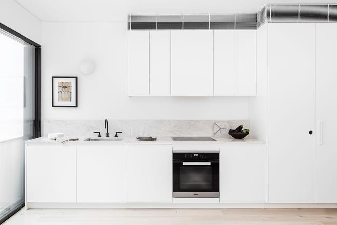 "The sleek and simple kitchen features White Emperador marble benchtops and timber cabinets in a polyurethane satin finish painted with Dulux 'Fair Bianca' half-strength. ""The result is an open, light and uncluttered space where simplicity is the ultimate sophistication,"" Cushla says."
