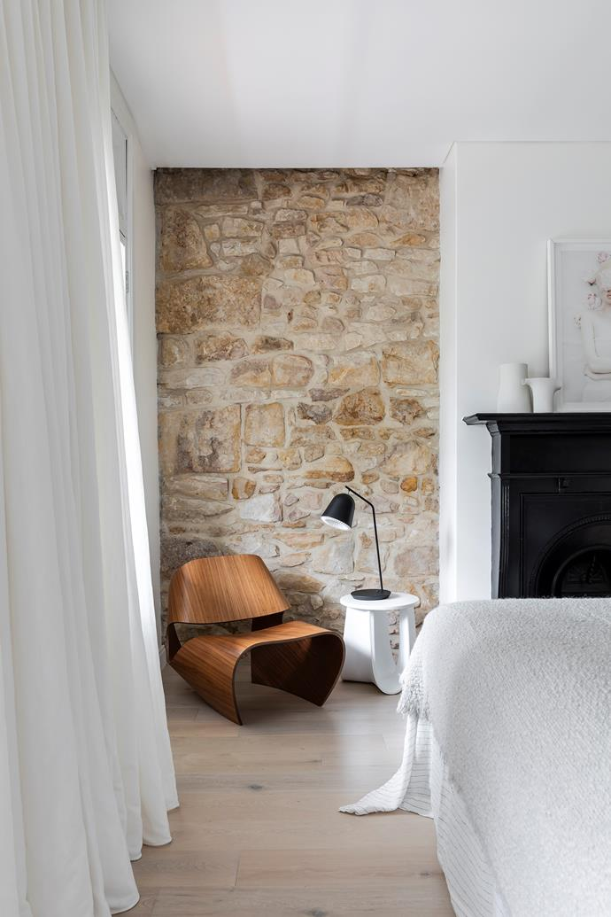 The original sandstone wall and fireplace make for one very charming bedroom. A Made In Ratio 'Cowrie' chair from Living Edge and side table from Hub Furniture provide a place to sit, while glass doors framed by sheer curtains lead out onto the terrace balcony.