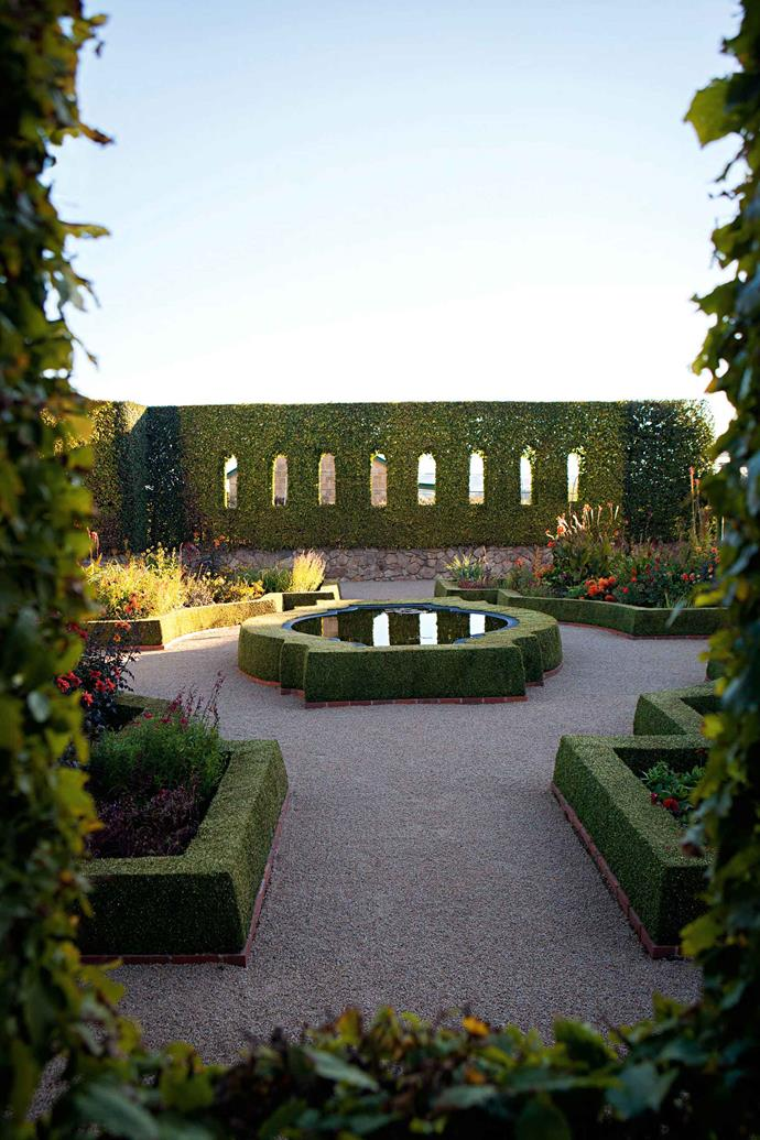 """The Sunken Garden at the centre of this area, right outside the front door, is outlined by the solid green of box while the beds are filled with flowers in hot colours, from dahlias to salvias, tulips and lilies, according to the season. From this starting point, the rest of the garden rooms beg to be explored. Steps lead through box-edged beds and a holly circle to a long, five-metre wide border which has been recently replanted. """"The tall hedges are of hornbeam (Carpinus betulus), a deciduous European tree that clips really wel,"""" says Craig. """"I've trained 'window' openings, inspired by French gardens that often have more architectural shapes in their hedges than English gardens."""""""