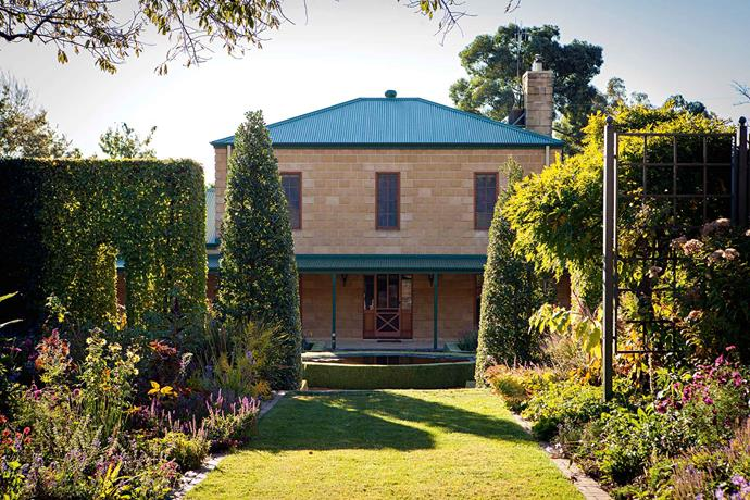 """The view walking down the drive takes in the vista of the [Georgian-style stone house](https://www.homestolove.com.au/1930s-georgian-brick-home-honours-late-designers-vision-5654