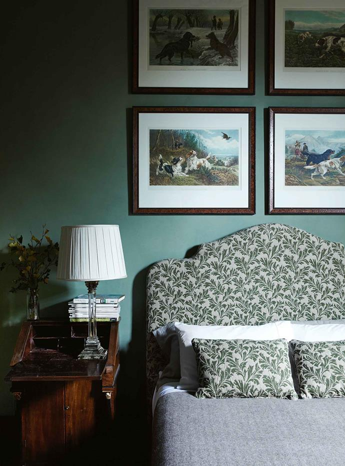 "The main bedroom is painted in [Farrow & Ball's](https://www.farrow-ball.com/|target=""_blank"") Calke Green. The prints above the upholstered bedhead were found in a Paris flea market. Nigel and Andrew did much of the painting and other work. Meanwhile, Stuart had shades made for lamps, and supplied fabric for upholstery and curtains. Known for his lush use of textiles, he was also practical. Red linen for curtains in the old bank chamber — a grand dining space with soaring ceilings now known as the 'party' room — was just $20 a metre. ""He said 'The make-up is the important thing',"" Nigel recalls."