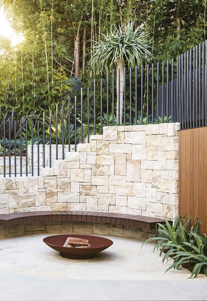 "A curved sandstone stairway connects the pool terrace at house level, which is the main entertaining area, to the lower garden. The inner curve of the staircase defines the [fire-pit](https://www.homestolove.com.au/best-fire-pits-under-100-6516|target=""_blank"") enclosure - an additional relaxation spot and feature of the lower garden, with a cantilevered floating bench in spotted gum that wraps around the space.<br><br>**Fire pit** ""Instead of using shards underfoot, we shaped the sandstone into circular pieces to give a softer feel."" An ashlar pattern features on the wall, while Screenwood cladding in western red cedar continues the curve."